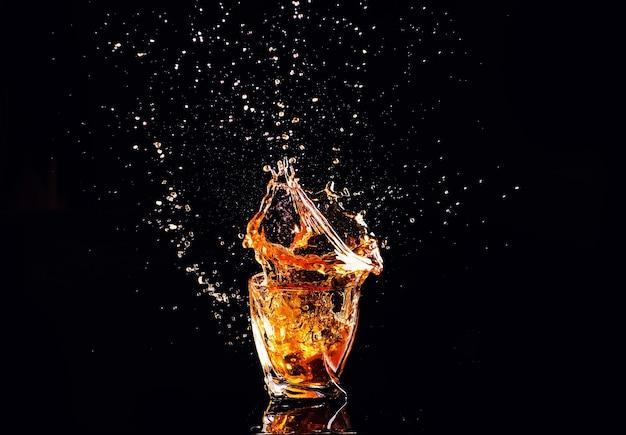 Whisky mit spritzer auf schwarzem hintergrund, brandy in einem glas