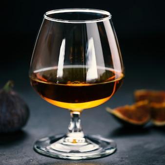 Whisky oder cognac in einem glas und feigen auf dunklem beton
