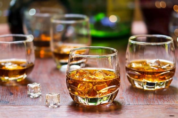 Whisky trinkt mit eis auf hölzernem hintergrund