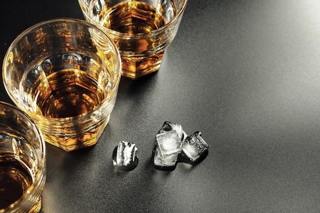 Whisky und eis auf rustikalem hölzernem hintergrund