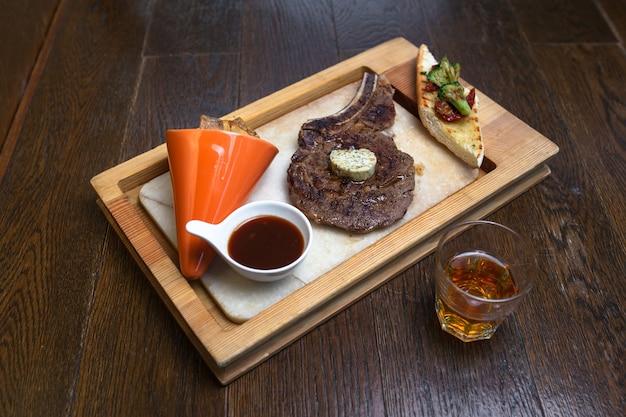 Whisky und steak mit sauce auf holz