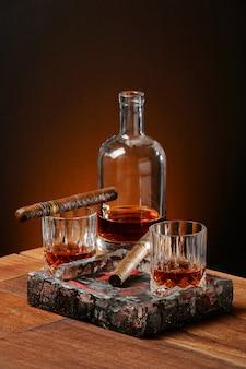 Whisky, zigarren und aschenbecher auf dem holztisch