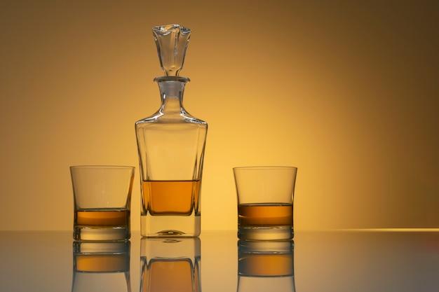 Whiskyflasche mit zwei gläsern mit reflexion auf glastisch und hellgelbem hintergrund