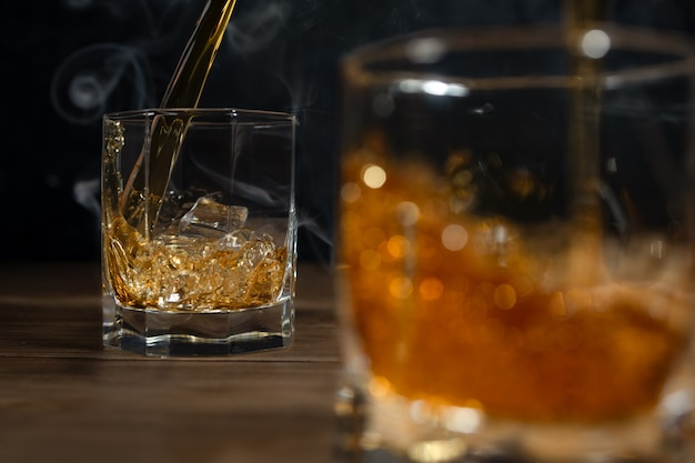 Whiskygetränke auf holz mit eiswürfeln und spritzer.