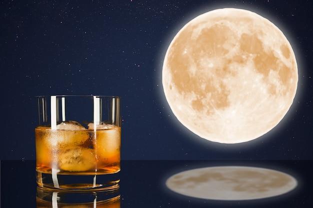 Whiskyglas am mitternachtshimmel mit vollmondhintergrund. cognac-glas. schnapsglas voll. cognac frankreich. vollmond und scotch drink. vollmond am nachthimmel. mystischer vollmond.