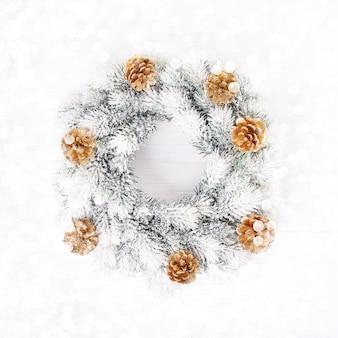 White christmas hintergrund. kranz der weißen weihnacht mit goldkegeln auf weißem hintergrund. platz kopieren