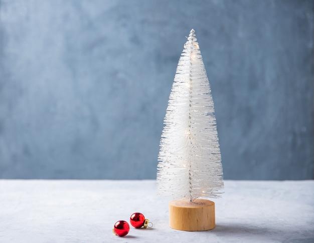 White christmas toy tannenbaum auf einem holzständer mit roten kugeln auf einem weißen tisch. vorderansicht und kopierbereich