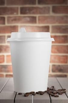 White paper cup auf einem holztisch, rote backsteinmauer im hintergrund. 3d-rendering.