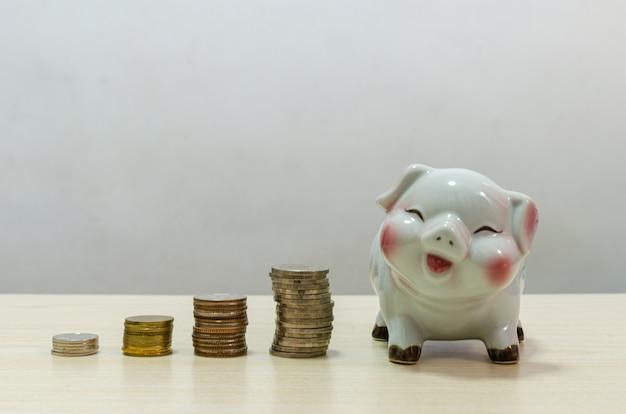 White pig sparschwein und münzen geld auf holztisch. konzept der finanzierung und geld sparen, investition oder rentenalter in der zukunft.