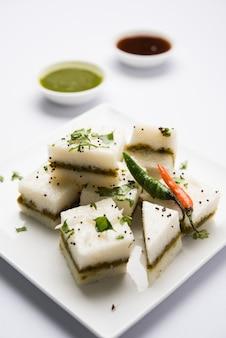 White sandwich dhokla ist ein indischer herzhafter snack aus kichererbsenmehl oder reismehl, ursprung in gujarat. serviert mit grünem und tamarinden-chutney. selektiver fokus