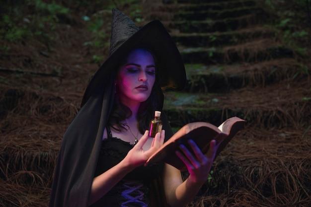 Wicca des jungen mädchens der halloweenhexe, das schwarzes kostüm trägt