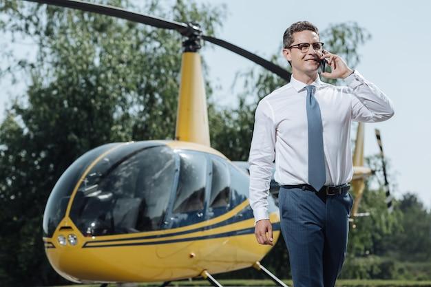 Wichtige diskussion. charmanter junger ceo, der details mit partnern am telefon bespricht und kurz davor steht, auf einem hubschrauberlandeplatz zu fliegen