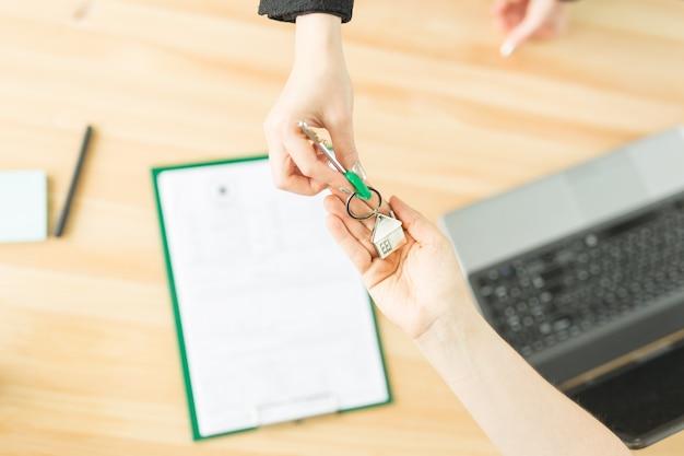Wichtige dokumente für den kauf eines immobilienobjekts und schlüssel aus einem neuen zuhause.