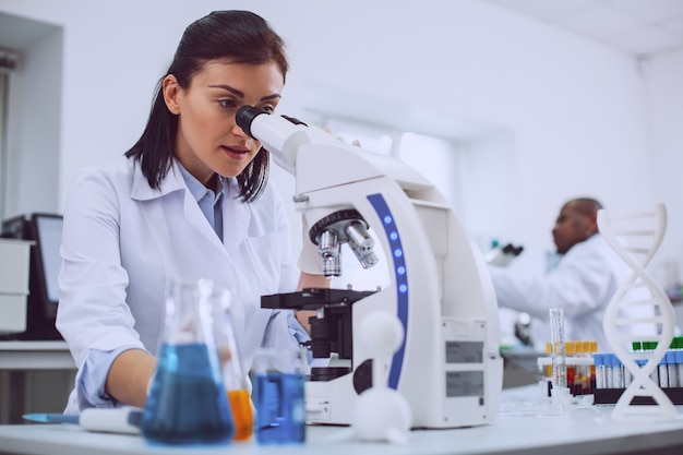 Wichtige forschung. ernsthafte erfahrene wissenschaftlerin, die mit ihrem mikroskop arbeitet und eine uniform trägt