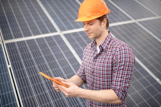 Wichtige informationen. interessierter mann in orangefarbenem schutzhelm mit blick auf tablet auf grauer oberfläche im freien