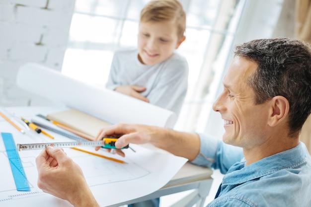 Wichtige maßnahmen. angenehmer junge vor zehn jahren, der im büro seines vaters am tisch sitzt und ihn beobachtet, wie er die maßnahmen auf dem band überprüft, während er an der blaupause arbeitet