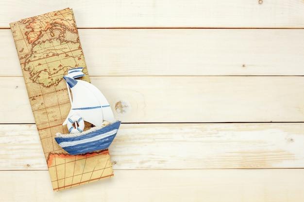 Wichtige reiseartikel der draufsicht. die bootskarte auf weißem hölzernem hintergrund mit kopienraum.