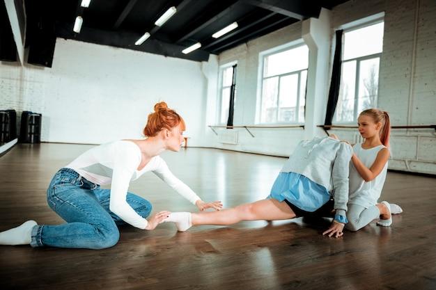 Wichtige übung. der rothaarige gymnastiklehrer trägt blue jeans und sieht konzentriert aus