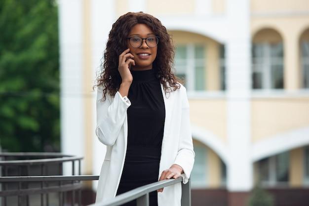 Wichtiger anruf. afroamerikanische geschäftsfrau in bürokleidung lächelnd, sieht selbstbewusst und ernst aus, beschäftigt. konzept für finanzen, wirtschaft, gleichstellung und menschenrechte. schönes junges modell, erfolgreich.