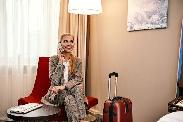 Wichtiger anruf. junge und stilvolle geschäftsfrau mit koffer und smartphone, die auf dem sofa im hotelzimmer sitzt