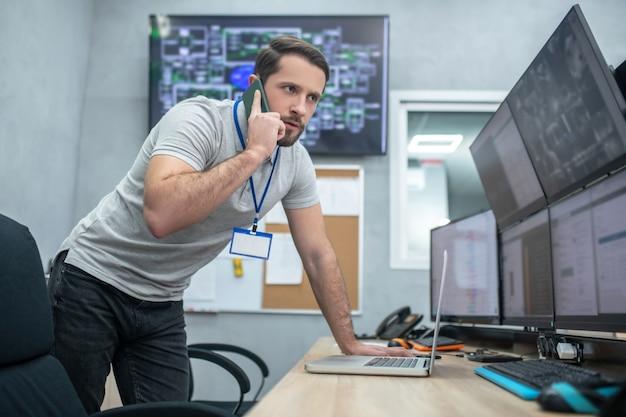 Wichtiger anruf. konzentrierter mann, der die monitore genau beobachtet und auf dem smartphone spricht, das sich über den tisch beugt