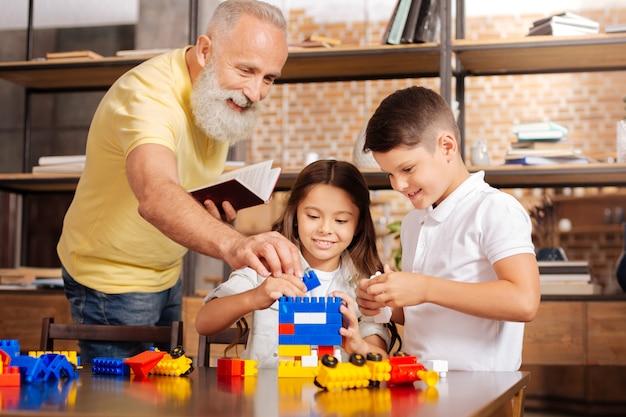Wichtiger beitrag. charmanter lächelnder älterer mann mit einem buch in den händen, das dem turm, der von seinen geliebten enkelkindern gebaut wird, ein weiteres bauelement hinzufügt