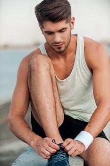 Wichtiges detail für schnelles laufen. nahaufnahme eines mannes, der beim sitzen im freien schnürsenkel an sportschuhen bindet