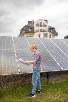 Wichtiges schema. profil eines mannes in schutzhelm, der sorgfältig die zeichnung untersucht, die in der nähe der oberfläche der solarbatterie auf dem territorium des landhauses steht