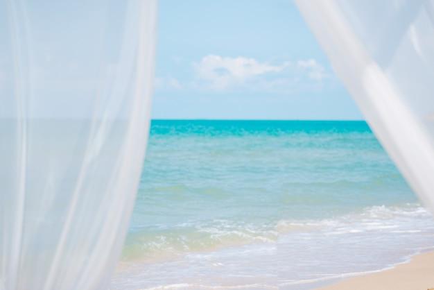 Wickeln sie weiße vorhänge des schlages auf sandmeer, sommerferienkonzept.