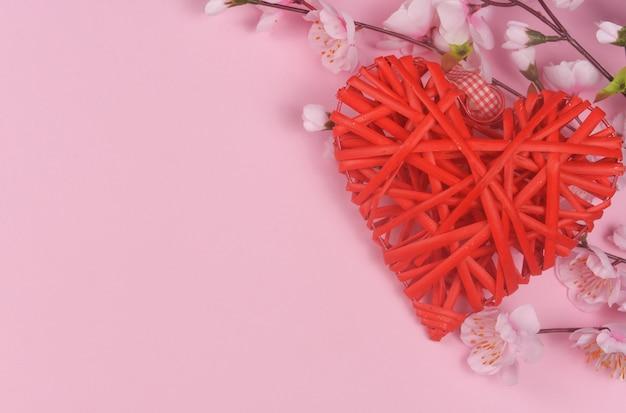 Wicker rotes herz mit rosa blumen auf einer rosa oberfläche