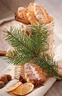 Wicker weihnachtsstrumpf gefüllt mit keksen, zimtstangen, kandierter zitrone und sternanis