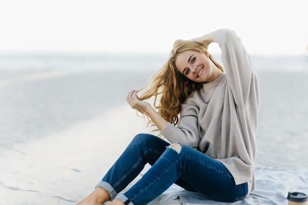 Wicklerin, die am herbststrand emotional aufwirft. außenporträt der hübschen lockigen frau in den jeans, die im sand sitzen.