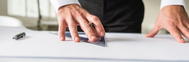 Wide view-bild des designers, der an einem projekt auf seinem schreibtisch mit großem papier, bleistift und lineal arbeitet.