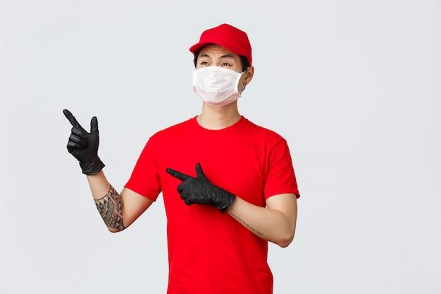 Widerstrebender und unzufriedener asiatischer lieferbote, der über großauftrag jammert und berg von kisten schaut. arbeiter der lieferfirma zeigt auf die obere linke ecke und verzieht das gesicht. kurier in medizinischer maske und handschuhen