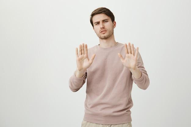 Widerstrebender unzufriedener mann, der ohne ablehnung die hand schüttelt