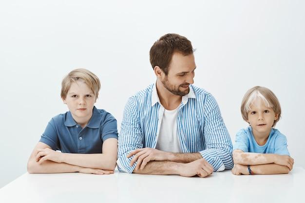Wie der vater wie die söhne. porträt der schönen glücklichen familie, die mit den händen zusammen sitzt