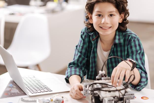 Wie ein kompetenter programmierer. lächelnder begabter fähiger junge, der im klassenzimmer sitzt und mit elektronischen geräten arbeitet, während er studiert und freude ausdrückt