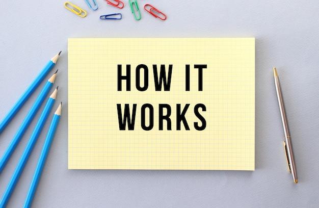 Wie es funktioniert text im notizbuch auf grauem hintergrund neben stiften, stift und büroklammern. konzept.