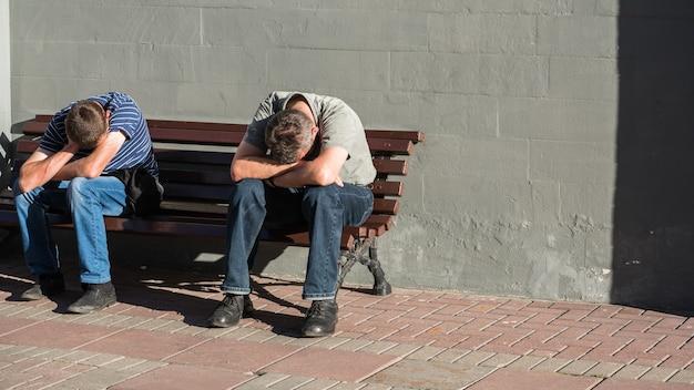 Wie fühlt sich der montagmorgen an? zwei nicht identifizierte männer mit dem gesicht nach unten auf den armen auf der arbat-straße, moskau, russland