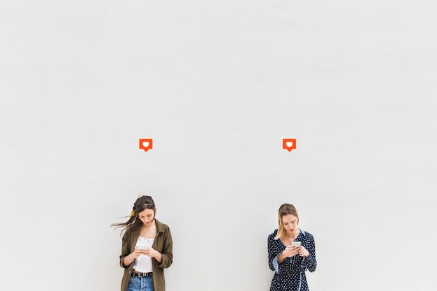 Wie ikone über den zwei jungen frauen, die mobiltelefone gegen weißen hintergrund verwenden
