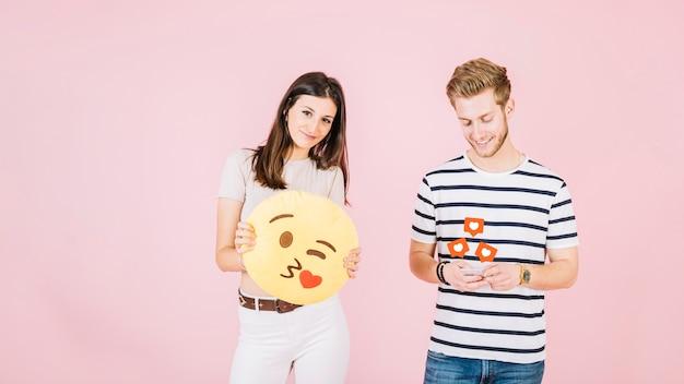 Wie ikonen über dem mann, der handy außer der frau verwendet, die kuss emoji hält