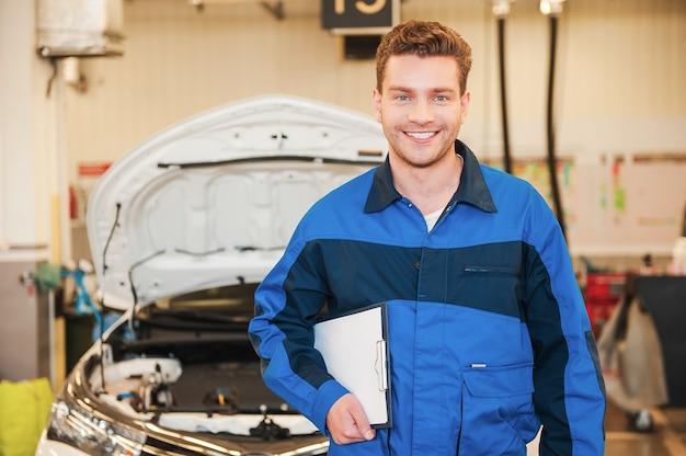 Wie kann ich dir helfen? hübscher junger mann in uniform, der klemmbrett hält und lächelt, während er in der werkstatt mit auto im hintergrund steht