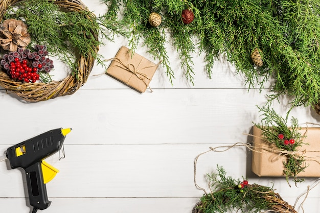 Wie man einen weihnachtstürkranz macht. der arbeitsprozess. der arbeitsplatz des dekorateurs. ansicht von oben. platz kopieren. stillleben. flach liegen.