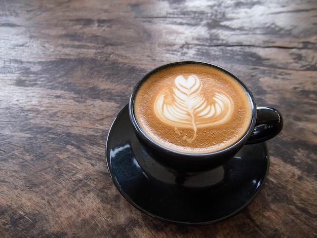 Wie man latte art kaffee in einer schwarzen tasse zubereitet, auf einen alten holztisch stellen. in einem café