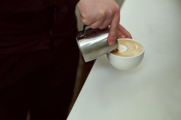 Wie man latte art von barista in milch und kaffee fokussiert