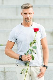 Wie man romantisch ist. romantischer herr. mann reifer selbstbewusster macho mit romantischem geschenk. hübscher kerl mit romantischem date der rosenblume. valentinstag und jubiläum. blumenlieferung. dating-dienste.