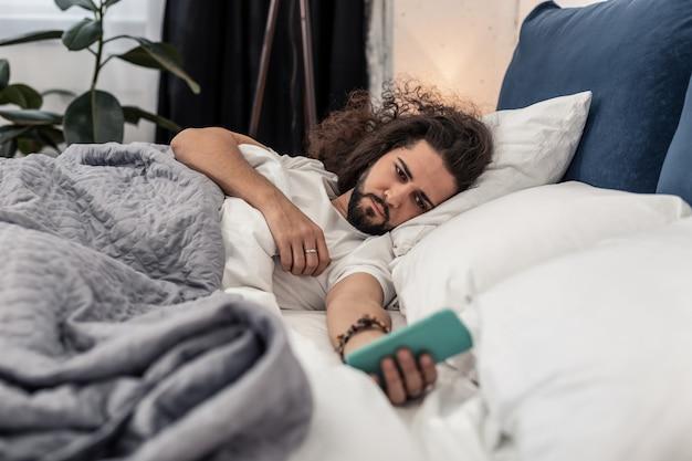 Wie spät ist es. fröhlicher, schläfriger mann, der sein smartphone hält, während er morgens die uhrzeit überprüft