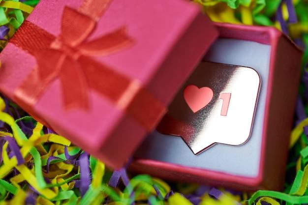 Wie symbol in geschenkbox. wie zeichenherzknopf, symbol mit herz und einer ziffer. social-media-network-marketing. mehrfarbiger lametta-hintergrund.