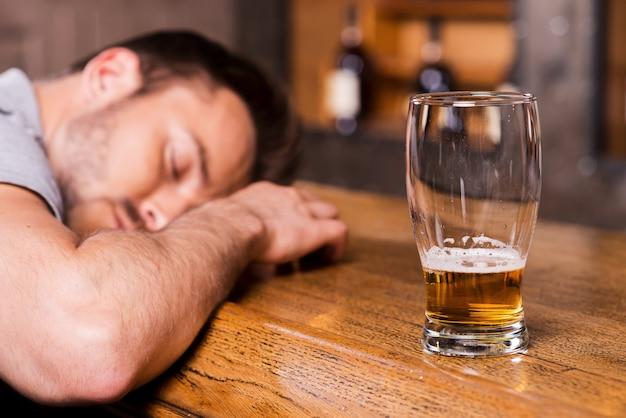 Wieder betrunken. betrunkener männlicher kunde, der sich an die bartheke lehnt und schläft, während glas mit bier in seiner nähe steht