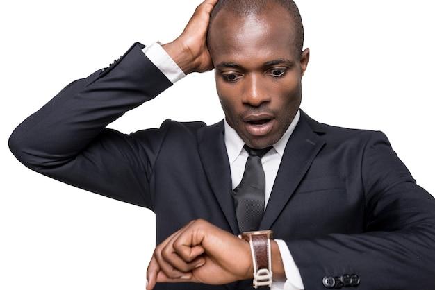 Wieder spät! besorgter junger afrikaner in formeller kleidung, der die zeit überprüft, während er auf seine uhr schaut und isoliert auf weißem hintergrund steht